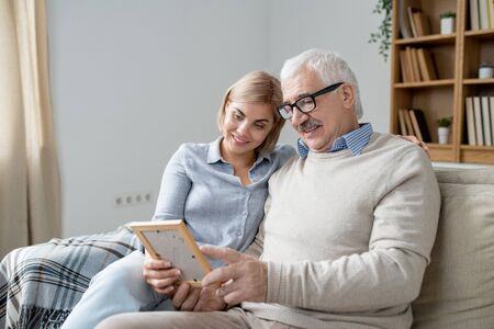 Senior man in casualwear showing his happy young daughter photo in frame Stock Photo