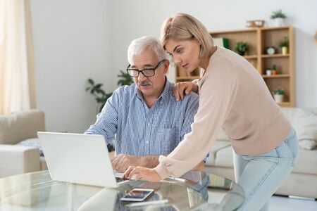 Young woman in casualwear and her senior father looking at laptop display