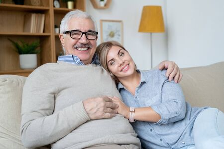 Pretty young smiling woman and her happy senior father relaxing on couch at home Stock Photo
