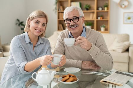 Happy young woman and her retired father holding cups of tea over served table Stock Photo