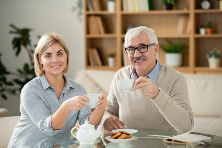 Smiling young woman and her senior father having tea by served table at home Stock Photo