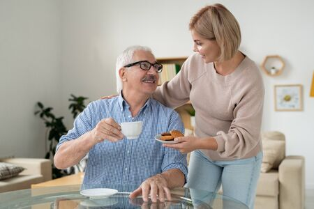 Careful daughter bringing cookies to her happy retired father with cup of tea Archivio Fotografico - 133482910