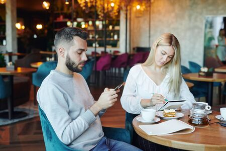 Serious man scrolling in smartphone on background of blonde girl making notes Archivio Fotografico - 133482911