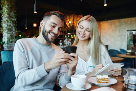 Young cheerful couple looking at smartphone screen while sitting in cafe Archivio Fotografico - 133482913