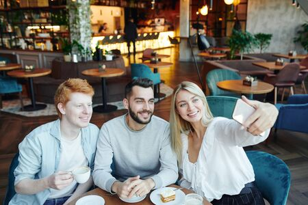 Three happy young friends sitting by table in cozy cafe and making selfie Archivio Fotografico - 133482920