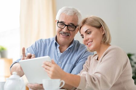 Senior grey-haired man and his pretty daughter watching online video in tablet