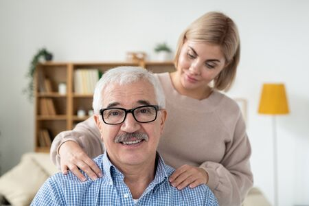 Careful young woman doing massage of shoulders to her senior father at home