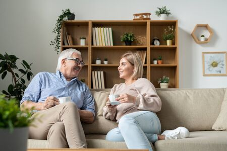 Young female and her father having tea while relaxing and chatting on couch
