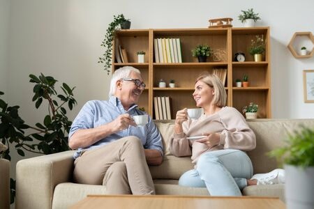 Happy female and her senior father having tea while sitting on couch and talking Stock Photo