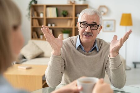 Aged man explaining something to his daughter while both having tea at home
