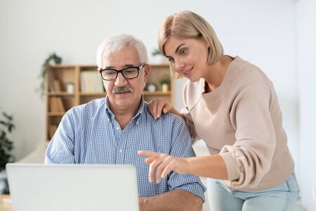 Young woman pointing at laptop display while explaining something to her father