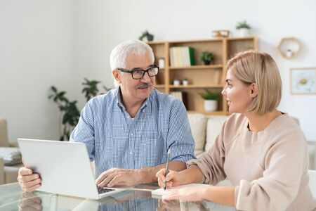 Young woman making notes in notepad while looking at senior father with laptop Stock Photo