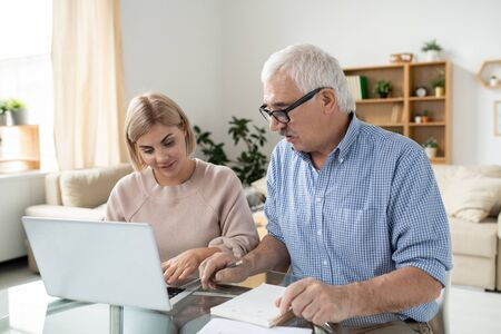 Pretty young woman with laptop and her retired senior father searching for data
