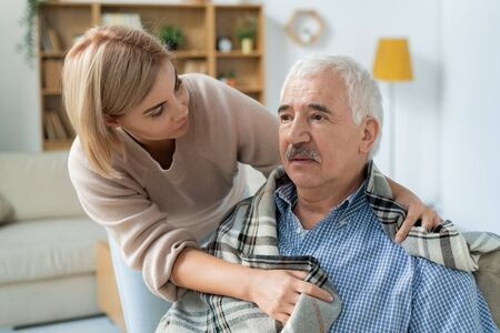 Careful and affectionate daughter taking care of her sick senior father at home Stock Photo