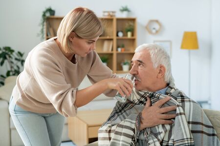 Young woman giving her sick father glass of water while taking care of him Stock Photo