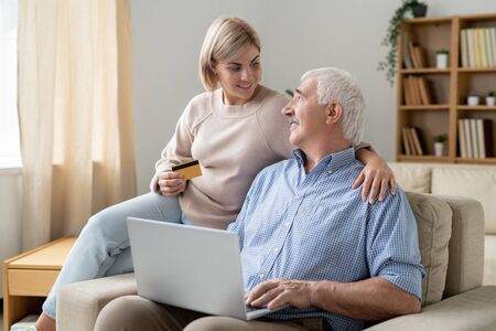 Pretty casual woman with credit card looking at her retired father with laptop