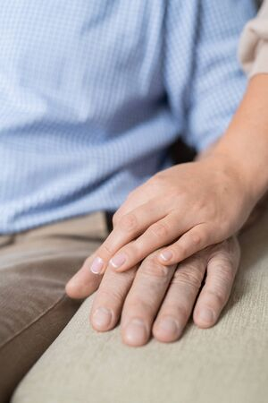 Hand of young careful and loving daughter on that of her sick retired father
