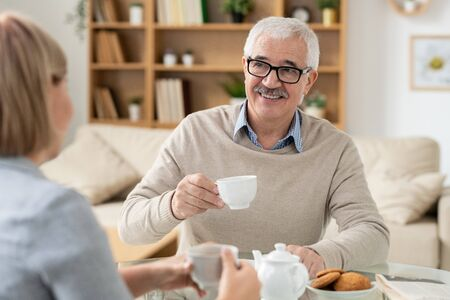 Happy retired man with cup of tea looking at his daughter during conversation