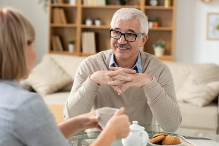 Senior retired man looking at his daughter with smile during chat by cup of tea