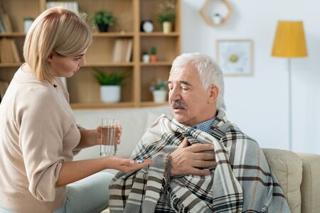 Sick senior man and his careful daughter bringing him glass of water and pills Stock Photo