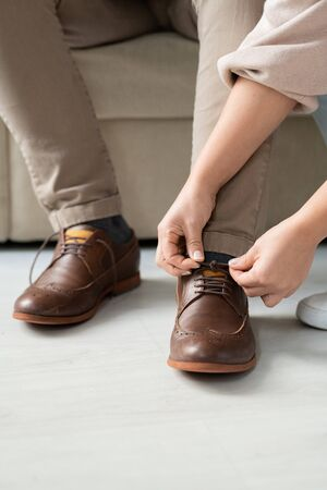 Hands of careful young daughter helping her sick father sitting on couch to tie shoelaces on brown boots before going out