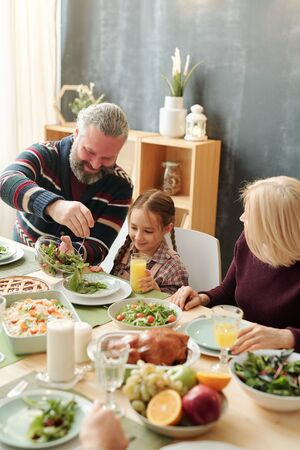 Happy mature man giving salad to his adorable granddaughter by festive table