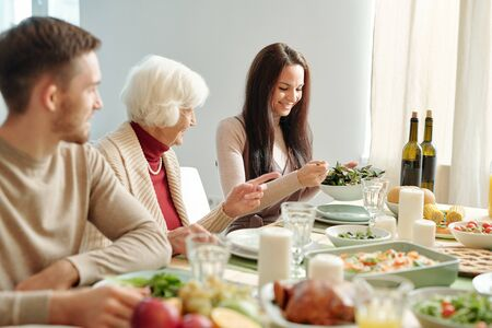 Happy young brunette woman putting salad on plate of grandma by dinner