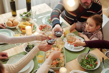 Hands of family of six clinking with drinks over festive table homemade food