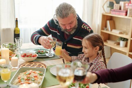 Senior man with glass of wine toasting with his granddaughter over served table Stock Photo