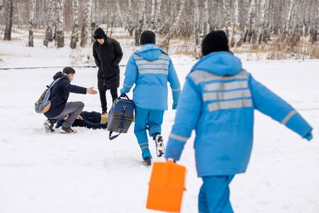 Rear view of paramedics in blue uniform hurrying to sick person lying in snow Standard-Bild - 133937452