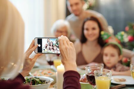 Hands of mature female holding smartphone while taking photo of her family