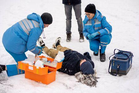 Group of young paramedics in winter uniform helping sick unconscious man Standard-Bild - 133937608
