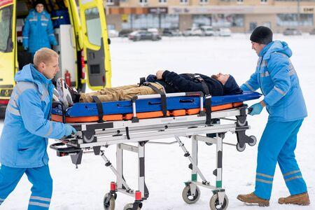 Dos paramédicos empujando a enfermo inconsciente en camilla hacia el coche de la ambulancia