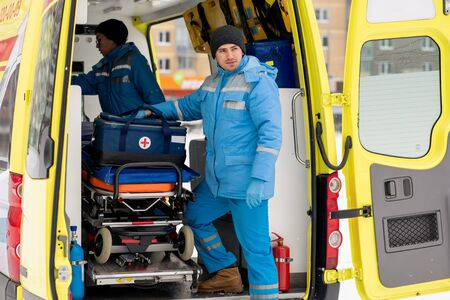 Male paramedic with first aid kit standing by stretcher in ambulance car Stock Photo