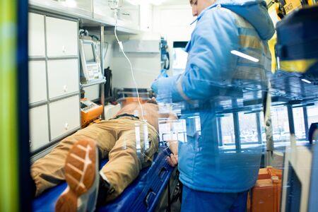 Paramédico de pie junto a la camilla con el hombre sin camisa enfermo y dándole primeros auxilios Foto de archivo