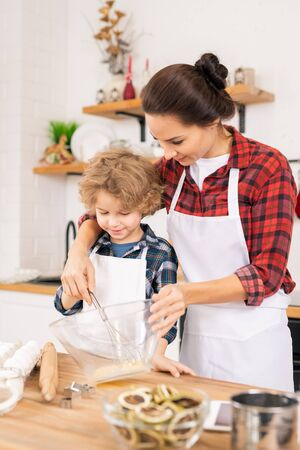 Young mother teaching little son how to shake raw eggs in bowl in the kitchen