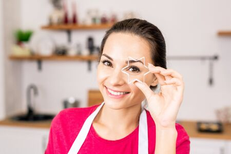 Young smiling woman holding star shaped cutter for homemade cookies by face