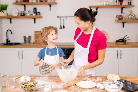 Happy boy with sifter looking at his mother whisking eggs with flour in bowl