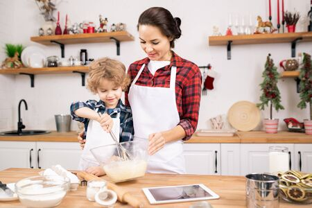 Little boy learning to whisk eggs for dough while standing close to his mother