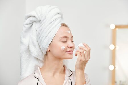 Pleased pretty girl enjoying smell of facial cream while taking care of her skin