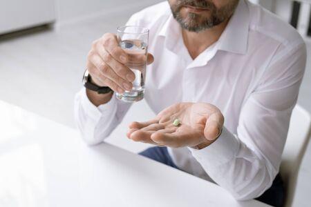 Elegant man in formalwear holding glass of water and painkiller over desk Stock fotó