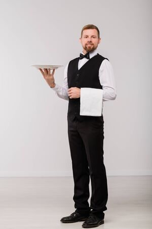 Happy young waiter in elegant suit and bowtie holding white towel and plate Stock Photo
