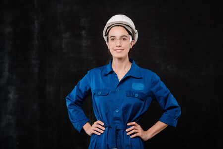 Pretty engineer in blue workwear and protective eyeglasses and helmet