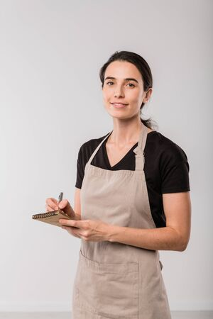 Pretty brunette waitress of cafe in apron making notes in small notepad