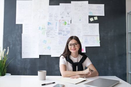 Young successful female economist sitting by desk on background of blackboard