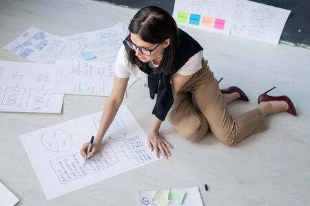 Young female broker in smart casual sitting on the floor and drawing diagrams of working points in office