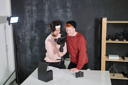 Two happy young male vloggers looking through new recorded video in camera