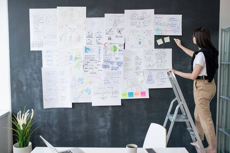 Young female economist with piece of chalk standing on step ladder in front of blackboard and writing down analysis Фото со стока