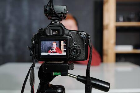 Videocamera con giovane vlogger maschio o fotografo con fotocamera sullo schermo
