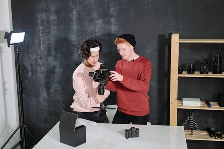 Two male vloggers in casualwear discussing new recorded video in studio